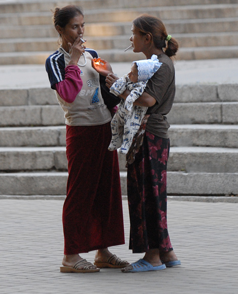 two beggar gipsy women smoking with a child in the ursu mihail