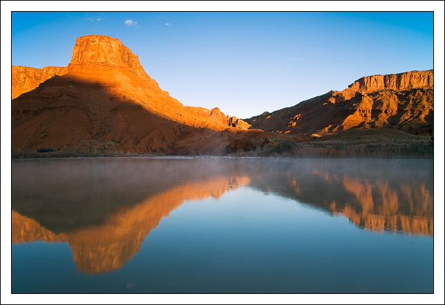 sandstone cliffs awash with alpenglow reflect in t edge bret