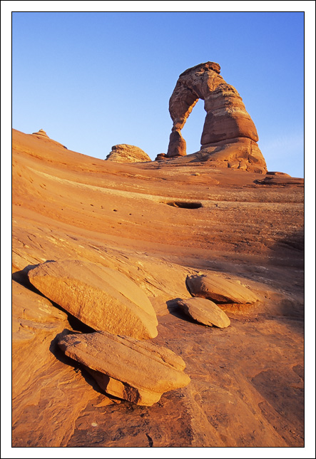 delicate arch and slabs of sandstone illuminated b edge bret