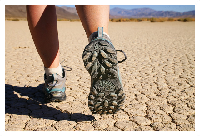 a hiker wanders across the cracked mud expanse of edge bret