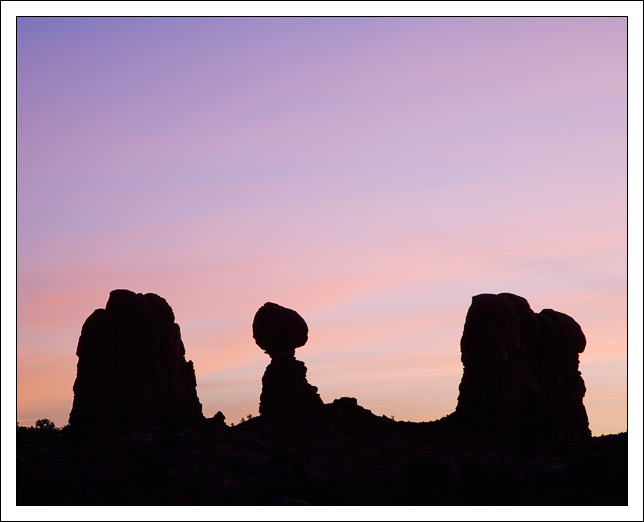 balanced rock is silhouetted against a pastel sky edge bret