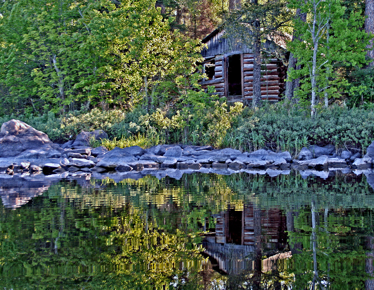 old cabin reflected as the sun rises through w pluskwik paul